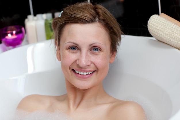 Jolly young woman having a bath