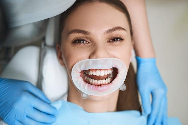 Веселая молодая женщина развлекается с открытым ртом в стоматологическом кабинете во время лечения зубов