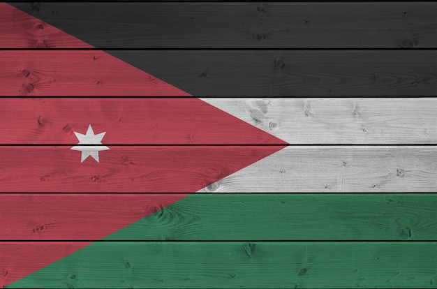 Jordan flag depicted in bright paint colors on old wooden wall. textured banner on rough background