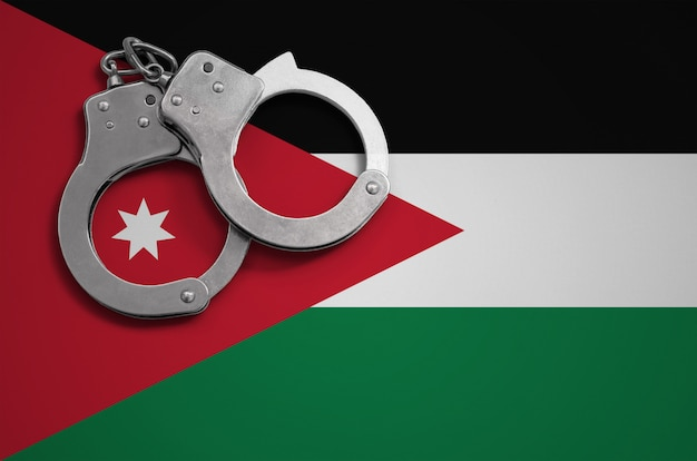 Jordan flag  and police handcuffs. the concept of crime and offenses in the country