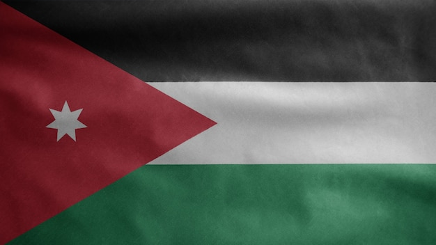 Jordan flag waving in the wind. close up of jordania banner blowing, soft and smooth silk. cloth fabric texture ensign background.