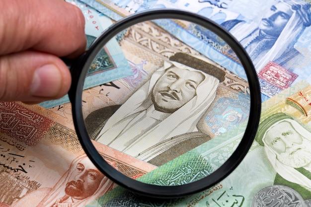 Jordanian dinar in a magnifying glass
