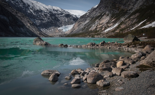 Jostedalsbreen 국립 공원. 노르웨이 jostedalen valley의 gaupne 마을 근처의 빙하 nigardsbreen, 자연 경관, 높은 봄 산에있는 돌 사이 청록색 빙하 호수
