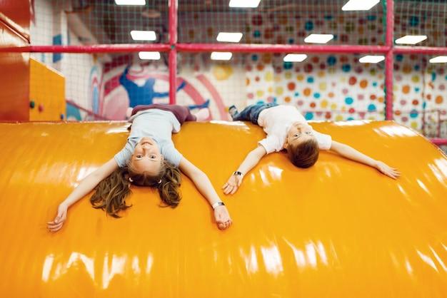 Веселые дети лежат на коврике в развлекательном центре.