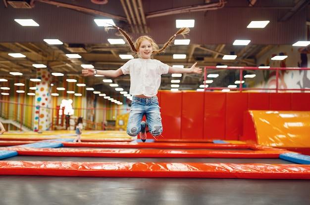 엔터테인먼트 센터에서 트램폴린에 점프 유쾌한 소녀. 휴일에 여자 아이 여가, 어린 시절의 행복, 놀이터에서 행복한 아이들