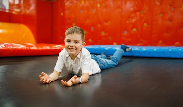 Веселый маленький мальчик, играющий на батуте в развлекательном центре. девочки отдыхают на праздниках, детское счастье, счастливые дети на детской площадке