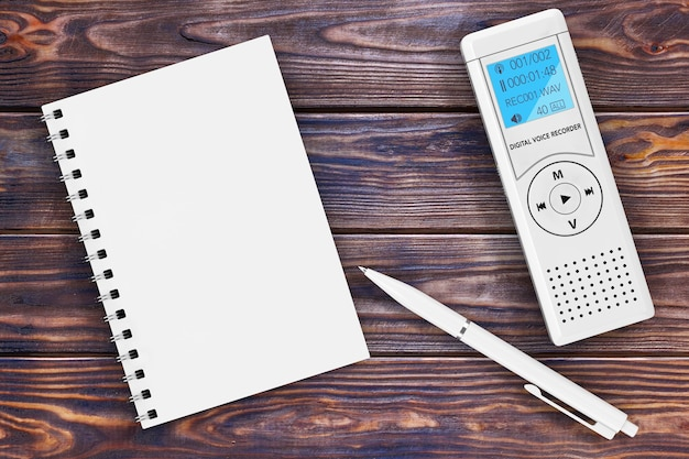 Journalist digital voice recorder or dictaphone, blank note pad and pen on a wooden table. 3d rendering