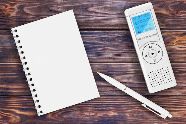 ジャーナリストのデジタルボイスレコーダーまたはディクタフォン、空白のメモ帳と木製のテーブル上のペン。 3dレンダリング