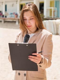 Журналистка стоит на пляже
