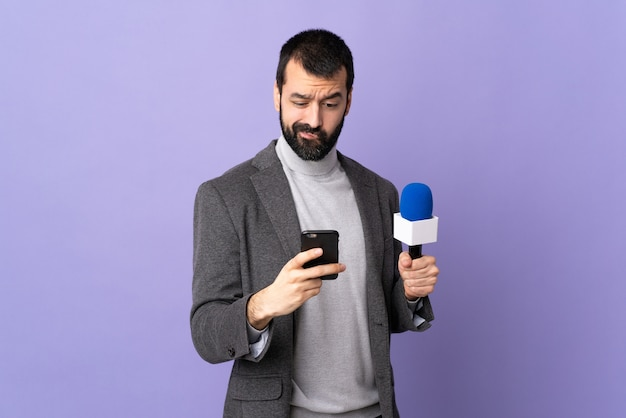 Журналист мужчина смотрит на телефон
