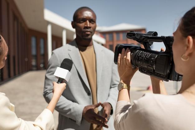 男性からのインタビューを受けるジャーナリスト
