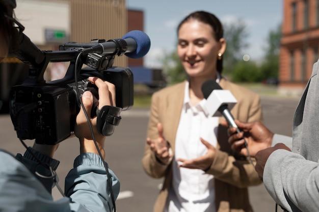 女性からのインタビューを受けるジャーナリスト