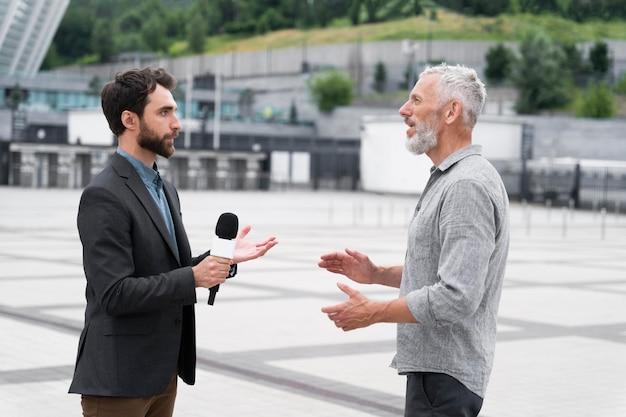 Giornalista che prende un'intervista da un uomo