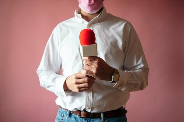 분홍색 배경으로 마이크 서와 마스크를 쓰고 기자