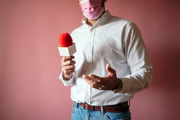 Журналист в маске с микрофоном, стоящий на розовом фоне