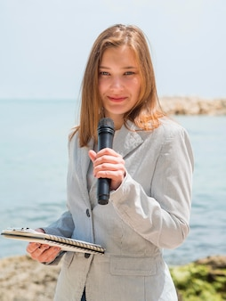 Journalist woman holding microphone at the sea
