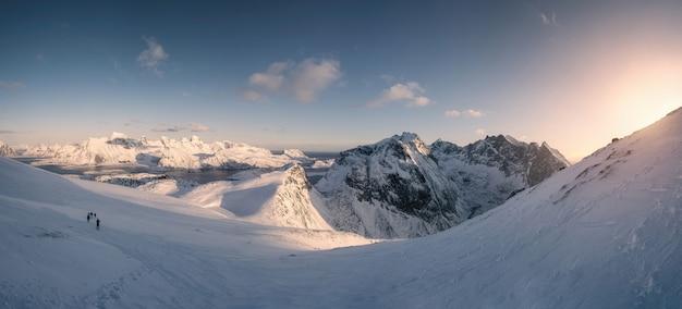 日没で雪に覆われた丘の上のグループ旅行者の旅