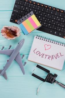 Планирование путешествия с туристическим снаряжением на макете вида сверху фона деревянного стола. раковина самолета и блокнот на синем столе.