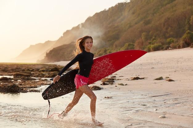 Концепция путешествия, отдыха и хобби. счастливая девочка-подросток в приподнятом настроении после серфинга