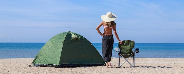 바다로의 여행. 해변에서 캠핑. 물로 휴가. 여자와 모래에 관광 의자와 텐트