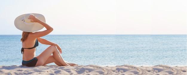 海への旅。ビーチで日光浴水着と帽子の女の子。砂の上に座っている観光客。レジャーウェア。コピースペース