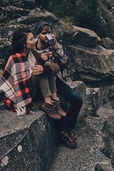 Поездки создают лучшие воспоминания. красивая молодая пара, покрытая одеялом, расслабляясь, сидя на скалах