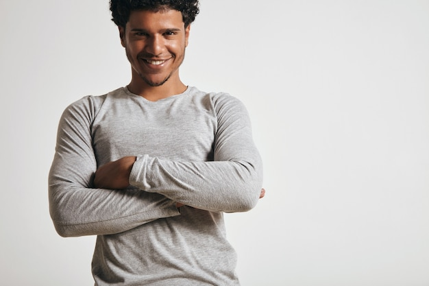 Jouyful smiling young latino guy in blank grey longsleeve folds hands on his chest
