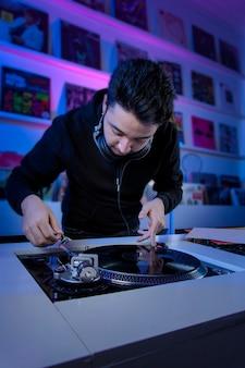Joven dj mezclando musica en una tienda de discos de vinilo usando un tornamesa de audio