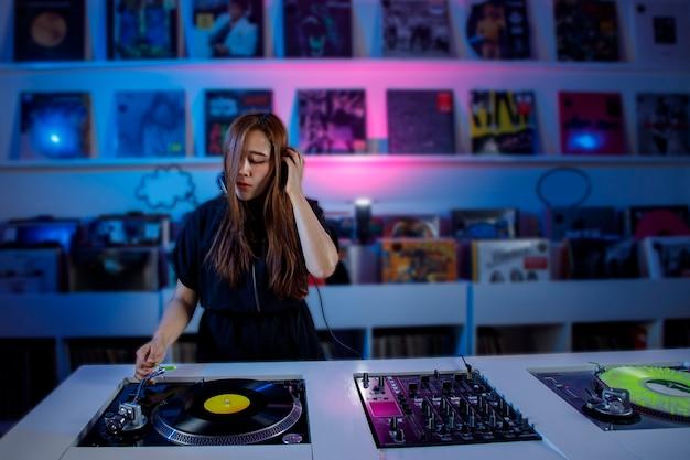 Joven mujer dj latina mezclando musica en una tienda de discos de vinilo