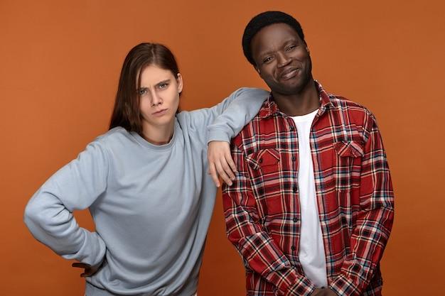 喜びと幸福の概念。で楽しんでいる愛の感情的な異人種間のカップル。彼の面白い白いガールフレンドが彼の肩に彼女の肘を置いている間笑っているハンサムな幸せな若い黒人の男