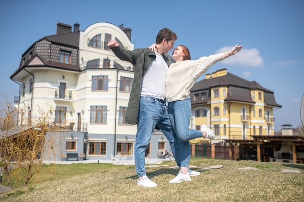 喜び。晴れた日に新鮮な空気の中で新しい建物の背景に立っている魅力的な男性を抱きしめる陽気なかなり長い髪の女性