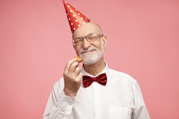 Concetto di gioia, divertimento, celebrazione e felicità. ragazzo di buon compleanno sulla settantina che ha un aspetto allegro