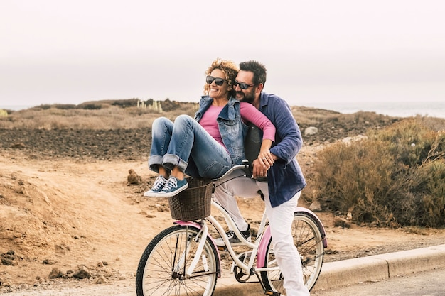 Joy and happiness for adult married couple start and have fun traveling on the same bike in outdoor activity with white sky on the background