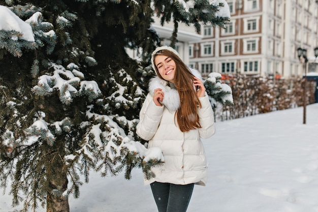 Joy, happiness of amazing beautiful girl smiling in warm winter clothes on fri tree full with snow space.