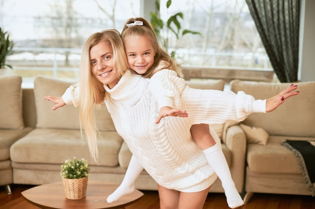 喜び、幸福、余暇の概念。腕を伸ばしたまま、母親の背中に乗った長い髪の可愛い女の子。居間で楽しんで、浮気している若いママと娘
