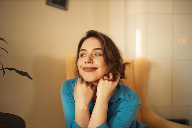 기쁨, 행복 및 휴식 개념. 그녀의 얼굴에 손으로 안락의 자에 편안하게 앉아 파란 드레스에 화려한 긍정적 인 젊은 여성의 초상화