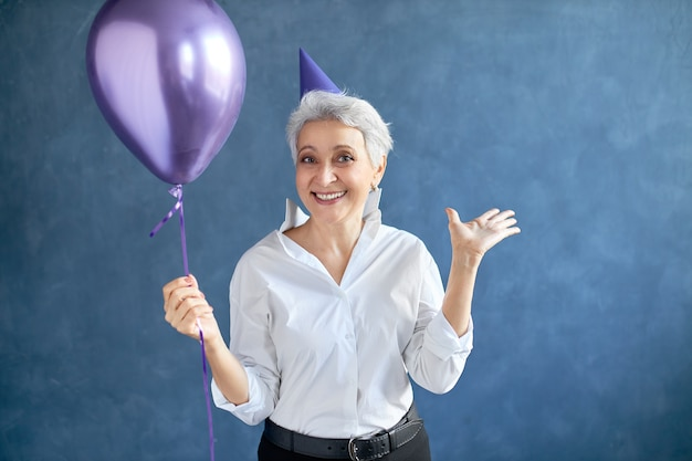 Joy, happiness, fun and positive emotions concept. portrait of beautiful excited 50 year old gray haired woman with conical hat on her head