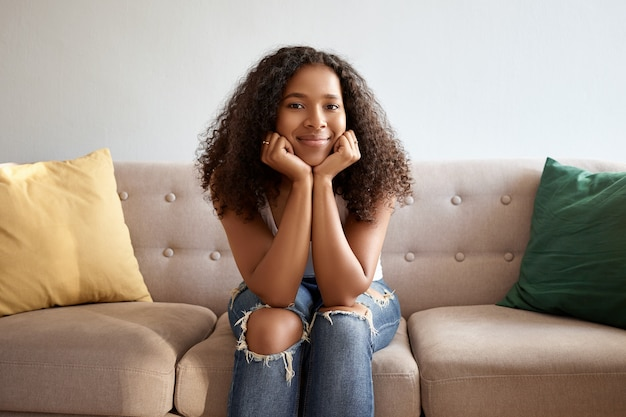喜び、幸福、余暇、そして前向きな感情。快適なソファの上のリビングルームでリラックスし、彼女のあごに手をつないで、幸せそうに笑っているスタイリッシュな服を着た魅力的な浅黒い肌の女の子