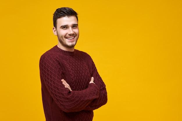 Gioia, felicità e reazione positiva. uomo europeo carismatico bello con un ampio sorriso radioso che posa al muro giallo vuoto con lo spazio della copia per il contenuto pubblicitario, tenendo le braccia conserte