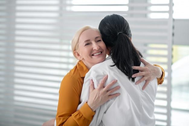 기쁨, 포옹. 흰색 코트에 그녀의 어깨 뒤에 또 다른 서 포옹 노란색 블라우스에 금발 성인 웃는 여자