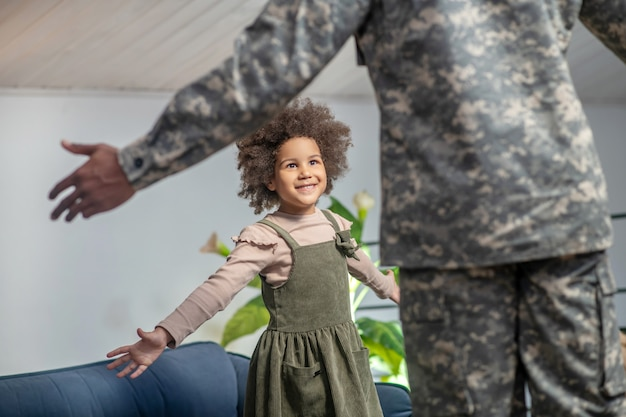 Joy, meeting. dad in military uniform with back to camera and dark-skinned little happy daughter holding hands to sides during meeting