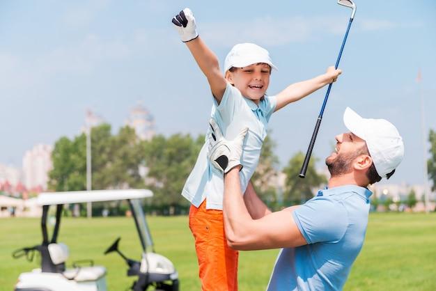 素晴らしいゲームの喜び。ゴルフ場に立っている間彼の息子を拾う興奮した若い男