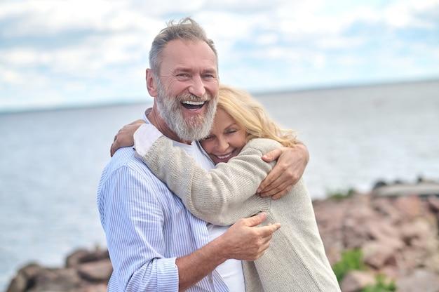 Радость жизни. довольный взрослый бородатый мужчина обнимает милую улыбающуюся женщину, стоящую на природе у моря