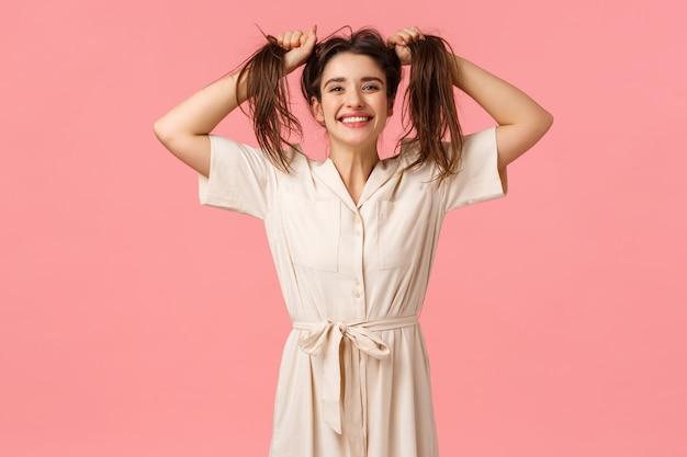 Концепция радости, вечеринки и счастья. глупая смешная женщина, весело дурачащаяся, дергающая волосы в сторону, делающая их грязными, улыбающиеся веселые, наслаждающиеся прекрасным днем, чувствуя себя веселыми и жизнерадостными, розовая стена
