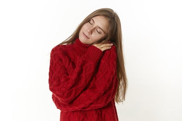 Концепция радости, релаксации и счастья. красивая юная леди в уютном свитере с длинными рукавами, обнимая себя и закрывая глаза от удовольствия и удовольствия, счастливо улыбаясь, наслаждаясь теплой одеждой