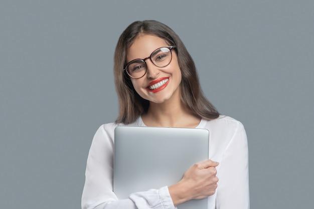 喜び、成功。自分自身にしっかりとラップトップを保持している眼鏡をかけて白い歯の笑顔で幸せな若いビジネス女性