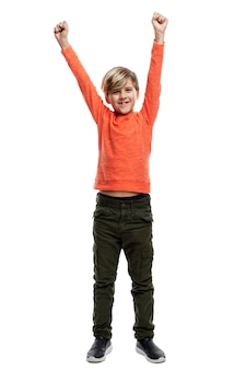 A joyful 9-year-old boy in an orange sweater and green trousers raised his hands up.