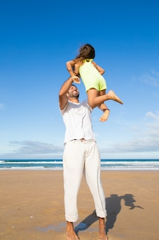 팔에 작은 딸을 들고 바다 해변에서 소녀와 함께 시간을 보내는 동안 공기에서 그녀를 들어 올리는 즐거운 활성 아빠