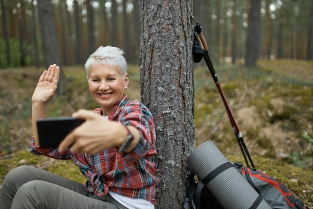Joyful active retired female sitting under tree with hiking gear holding cell phone, smiling and waving hand, talking to her friend via video conference call using online app.