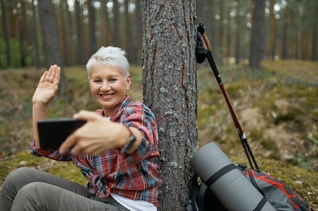 Радостная активная пенсионерка сидит под деревом с походным снаряжением, держит сотовый телефон, улыбается и машет рукой, разговаривает со своим другом по видеоконференции с помощью онлайн-приложения.